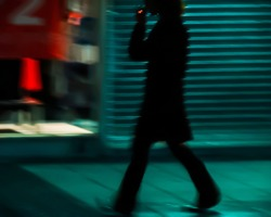 blurred silhouette of smoking young fellow walking along the show-window of closed shop; red light of a cigarette; relaxed gait; night city street in neon lights; roller shutters door; shot in motion