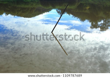 Blurred silhouette reflection in water waves trees sky clouds. #1109787689