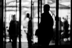 Blurred silhouettes of people in the business center. lobby in the rush hour is made in the manner of blur. silhouettes of people as they move, for the blurred background. black and white photo