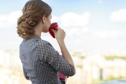 Blurred sky and city on background, attractive brunette caucasian business lady in patterned dress and watch stand on the roof and hold red paper folder and red cup,  look at far