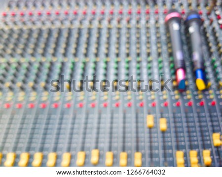 Blurred soft of microphone with audio sound mixer and amplifier equipment, a sliders of a mixing console. It is used for audio signals modifications to achieve the desired output #1266764032