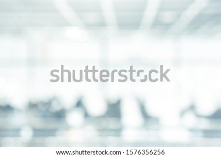 BLURRED SPACIOUS OFFICE BACKGROUND, MODERN BUSINESS HALL, BIG LIGHT INTERIOR WITH GLASSY WINDOWS AND BLURRED PEOPLE