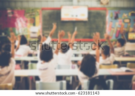 blurred student hands up asking ...