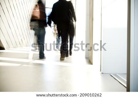 Blurred students walking in school corridor