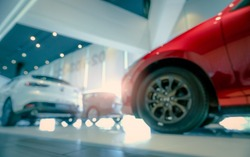 Blurred SUV car parked in modern showroom. Car dealership and auto leasing concept. Automotive industry. Modern luxury showroom. Rear view new car parked in showroom. Electric automobile technology.