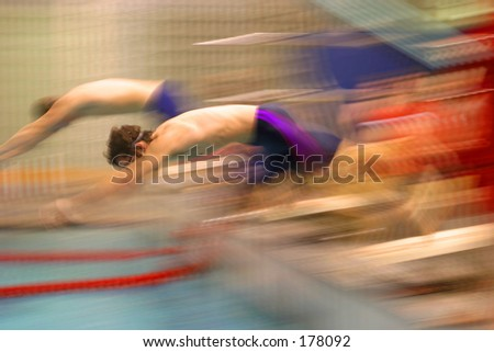 Blurred swimmers diving into a pool. - stock photo