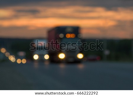Blurred texture Traffic trucks with glowing lights on the highway after sunset. Lights of searchlights. Route, road, transport. Blue and orange bright sky at dusk.