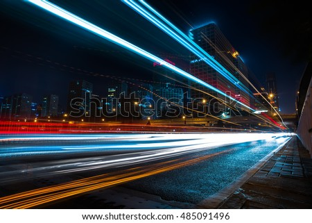 blurred traffic light trails on road at night in China. #485091496