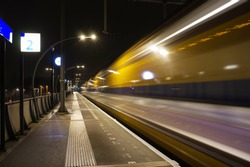 Blurred train by motion at night at station Arnhem south, Netherlands