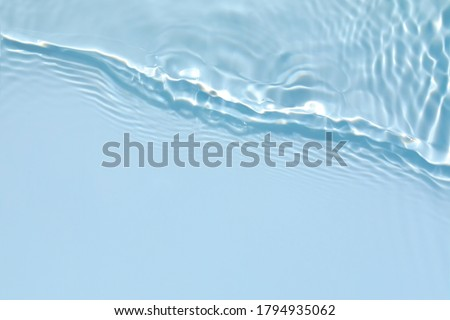 Blurred transparent blue colored clear calm water surface texture with splashes and bubbles. Trendy abstract nature background. Water waves in sunlight with copy space.