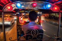 Blurred travel backgrounds - Riding Tuk Tuk at night in Bangkok, Thailand - popular among tourists city taxi