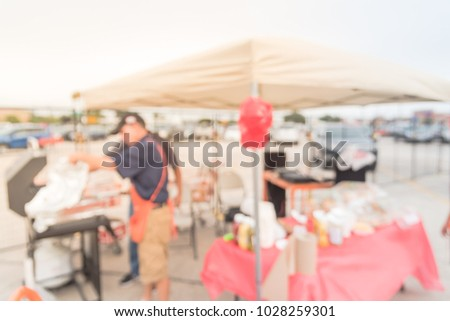 Blurred unidentified cook with apron grill meat skewers at community event tent in Houston, Texas, USA. Defocused people enjoy outdoor barbecue, lunchtime cookout, party and festival concept