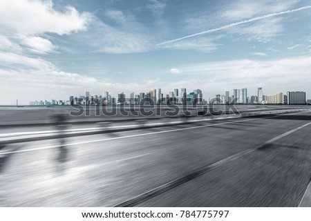 blurred urban traffic road with cityscape in background, China