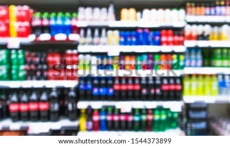 Blurred variety of soft drinks,energy drinks and sport drinks on shelves at grocery store supermarket. blurred effect display background, Drink section.