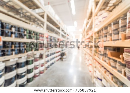Blurred verity of wall, floor, interior, exterior paint/stain cans and supplies at home decor department in large home improvement, hardware store in USA. From floor to ceiling shelf product display