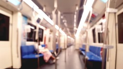 blurred view, inside of mrt train with only one girl sitting alone at night.