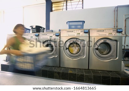 blurred view of a young woman doing laundry in a Laundromat