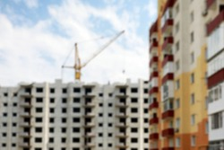 Blurred view of buildings and construction crane outdoors