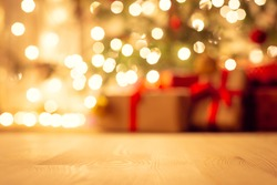 Blurred view of christmas tree in bright warm lights and beautiful presents under it, focus on the floor. Festive atmosphere, new year holidays background.