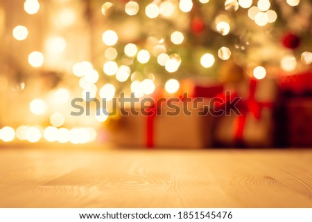 Photo of  Blurred view of christmas tree in bright warm lights and beautiful presents under it, focus on the floor. Festive atmosphere, new year holidays background.
