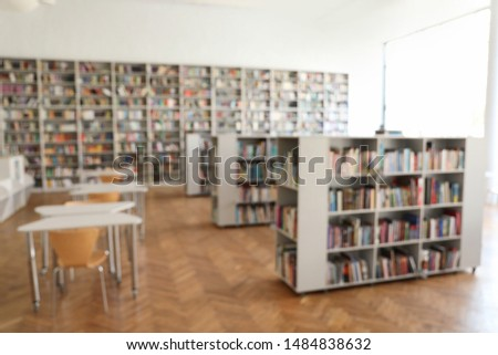 Blurred view of library interior with bookcases and tables #1484838632