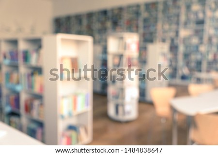 Blurred view of library interior with bookcases and tables #1484838647