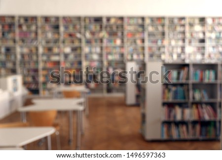 Blurred view of library interior with bookcases and tables #1496597363