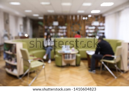 Blurred view of library interior with round sofa set and bookcases #1410604823