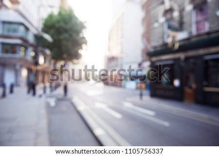 Blurred view of London street with shops, trees and buildings. Can be used as background  #1105756337