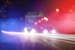 Blurred view of police cars on street at night