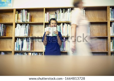 Blurred view of young boy holding up book smiling while librarian walks past