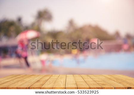 blurred Vintage tone picture of Empty wooden table on swimming pool background , rest and relax concept
