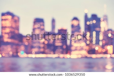 Blurred vintage toned picture of Manhattan skyline at dusk, abstract urban background, New York City, USA.