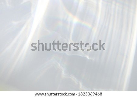 Blurred water texture overlay effect for photo and mockups. Organic drop diagonal shadow and light caustic effect on a white wall. Shadows for natural light effects