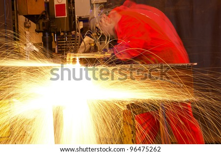 Blurred welder busy in workshop manufacturing metal construction. Many sparks shower from the torch.