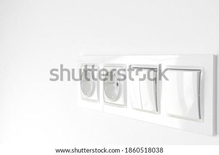 Blurred. White plastic walk-through switches and sockets on a white wall Сток-фото ©