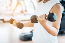Blurred Woman Lifting Dumbbells in Weight Training Fitness - Sport and Lifestyle Concept