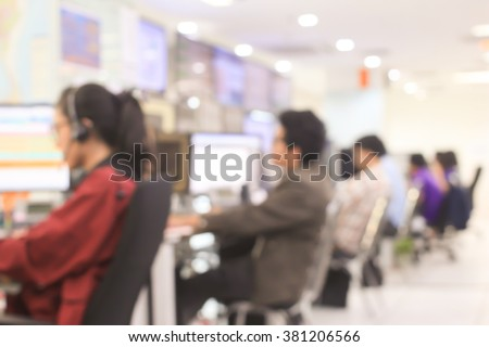 blurred woman/man operator working or searching on computer at office room:blur of woman monitoring and talking on headphone concept:blurry of people,business,technology :call centre help desk concept