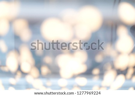 Blurred yellowish light on gray background. Soft blurry background with blurry city screen behind.