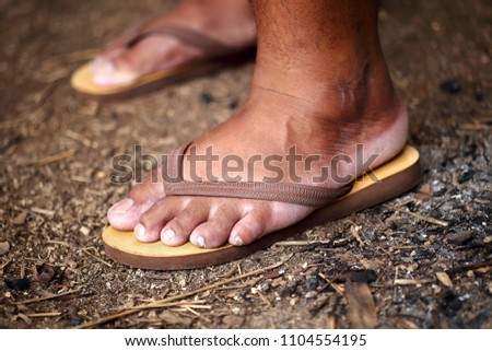 Blurring the feet of an old man wearing sandals walking, stomping on the ground.
