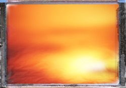 Blurry abstract background in red, yellow and orange post processed with antique frame concept of sunrise or sunset with space for runaround or wraparound text