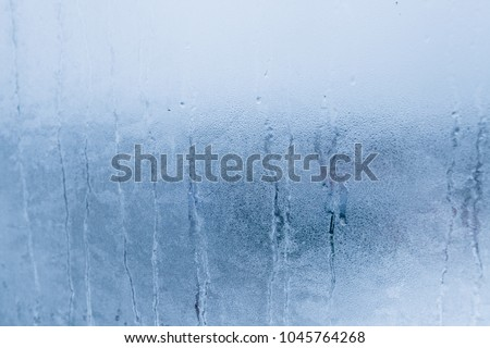 Blurry abstract background of foggy condensation on window glass natural surface. High humidity with formation of water droplets
