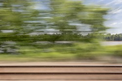 blurry abstract landscape of rail tracks and a river seen from train window in motion