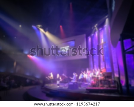 Blurry abstract worship band and the choir at Bible Church in Texas, USA. Dark background, smoke, concert spotlights for Christian concept. Worship lyric projection #1195674217