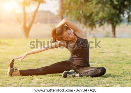 Blurry and soft focus of Athletic woman asia warming up and Young female athlete sitting on an exercising and stretching in a park before Runner outdoors, healthy lifestyle concept