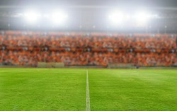 blurry and soft focus of football stadium and arena soccer field championship win for background