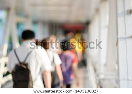 blurry background crowd enonymous walking on skywalk way in city with people walking into shopping mall or exhibition hall.