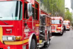 Blurry background of modern red firetrucks parked along a city street, in a first responder scene with space for text on the right