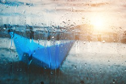 Blurry background with sunlight on water of blue paper boat washed up on beach after rain behind wet glass in raindrops