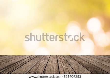 Blurry bokeh nature autumn season background with wood table top floor.montage picture for advertising or promote product.